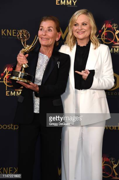 Judge Judy poses with the Lifetime Achievement Award in the press room with Amy Poehler during the 46th annual Daytime Emmy Awards at Pasadena Civic...