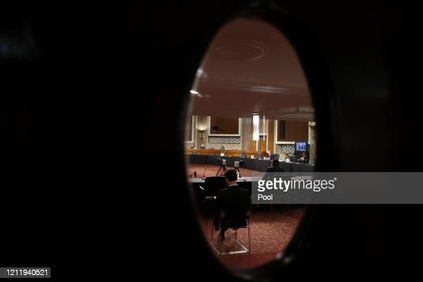 Judge Justin Walker is seen through the glass window of a closed door as he testifies before just a few senators during his US Senate Judiciary...
