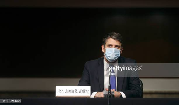 Judge Justin Walker wears a protective face mask as he sits in a sparsely attended hearing room due to social distancing measures because of the...