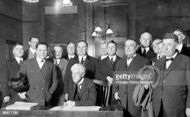 Judge Kenesaw Mountain Landis commissioner of baseball from 1920 to 1944 sits in a Chicago courtroom surrounded by Connie Mack Phil Ball Barney...