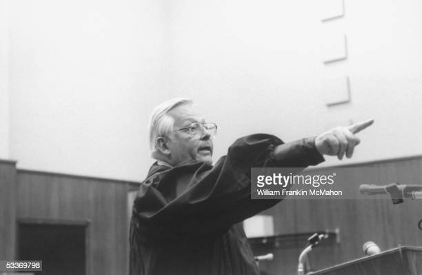 Judge Larry Gram pointing at an unseen reporter as he designates the next question while standing at podium in his courtroom during press conference...