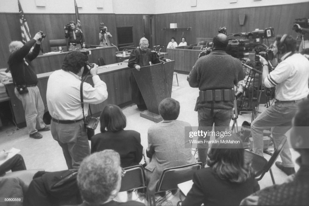 Judge Larry Gram standing at podium in front of the bench in his courtroom, speaking to the reporters & cameramen surrounding him at press conference after sentencing serial killer Jeffrey Dahmer.