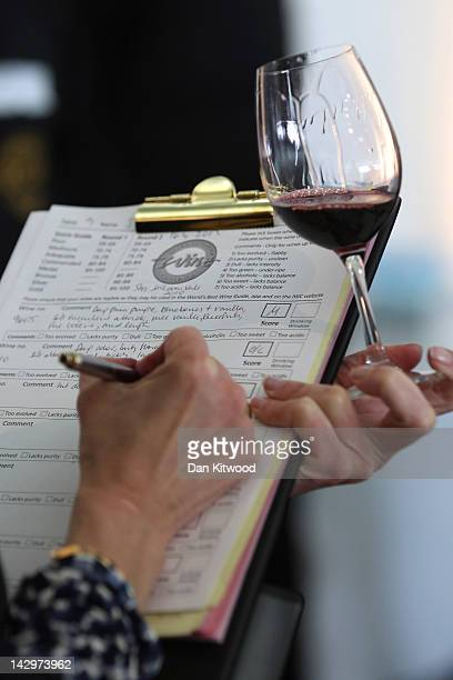 A judge marks a red wine at the 'International Wine Challenge' event at Lords Cricket ground on April 16 2012 in London England Judges will taste...