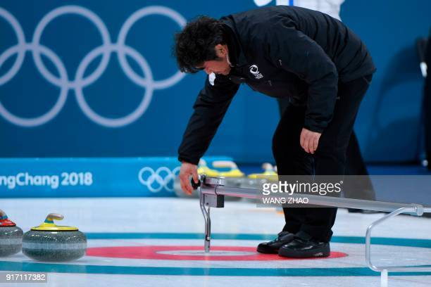 A judge measures during the curling mixed doubles tiebreaker game during the Pyeongchang 2018 Winter Olympic Games at the Gangneung Curling Centre in...