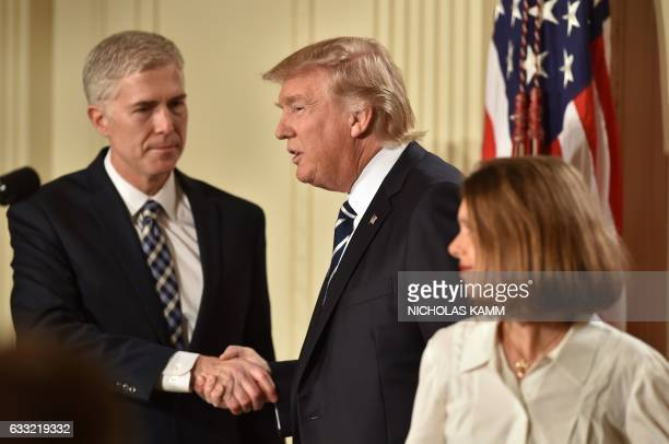 Judge Neil Gorsuch shakes hands with US President Donald Trump after he was nominated for the Supreme Court as his wife Marie Louise looks on at the...