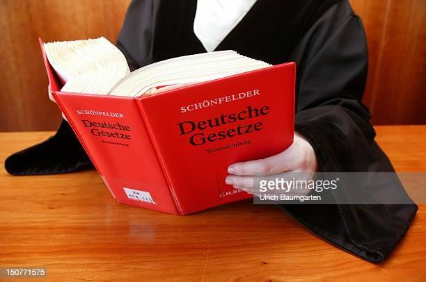 Judge / public prosecutor / lawyer wearing a robe holding the Schoenfelder code of law Deutsche Gesetze