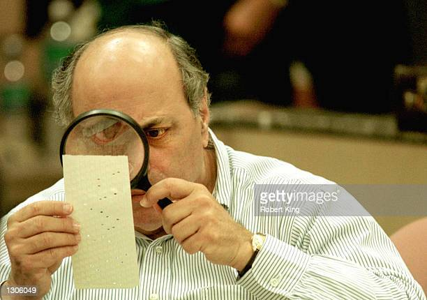 Judge Robert Rosenberg of the Broward County Canvassing Board uses a magnifying glass to examine a dimpled chad on a punch card ballot November 24...
