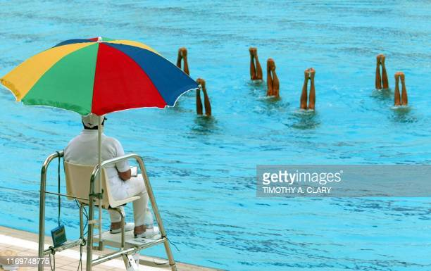 Judge under a beach umbrella stays out of the sun as she watches the Venezuela Team perform their routine during the Synchronized Swimming Team...