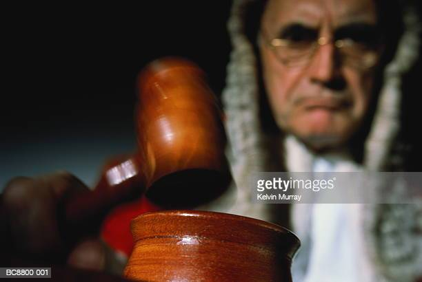 Judge using gavel in court (focus on foreground, blurred motion)