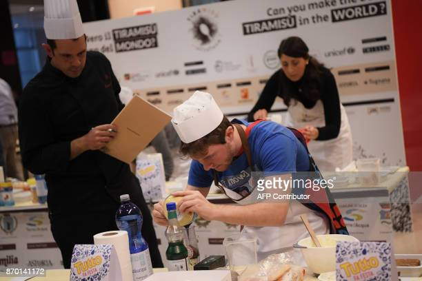 A judge watches as a competitor mixes ingredients together during the First Tiramisu World Cup on November 4 2017 in Treviso / AFP PHOTO / MARCO...