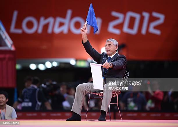 A judge waves a blue fleg indicating the victory of Korea's Cho JunHo in the men's 66kg quarter final match against Japan's Masashi Ebinuma in the...