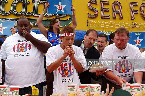 Judges and fellow contestants watch as Takeru Kobayashi of Japan eats his 31st hot dog July 4 2001 at the 86th annual Nathan''s Famous International...