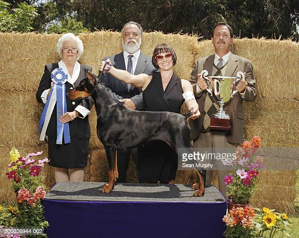 judges and owner with winning doberman pinscher at dog show - dog show stock pictures, royalty-free photos & images