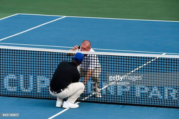 Judges check the net height prior to the Americas Zone Group I 2nd round Davis Cup tennis doubles match between Colombia's tennis players Juan...
