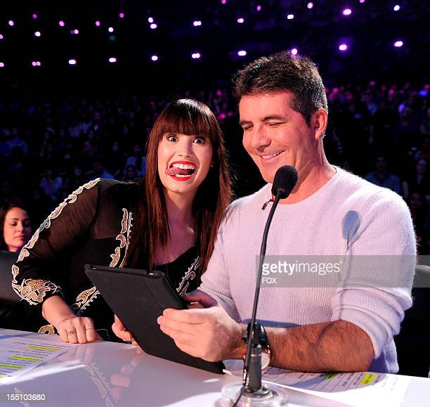 """Judges Demi Lovato and Simon Cowell on FOX's """"The X Factor"""" Season 2 Live Performance Show on October 31, 2012 in Hollywood, California."""