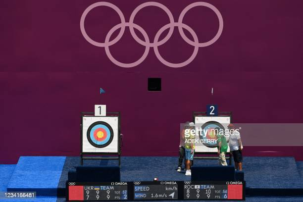 Judges examine a target in the women's team eliminations during the Tokyo 2020 Olympic Games at Yumenoshima Park Archery Field in Tokyo on July 25,...