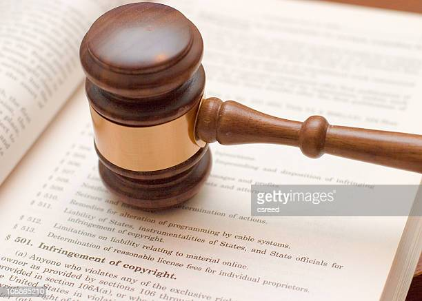 judges gavel on book about copyright infringement  - intellectual property stock pictures, royalty-free photos & images