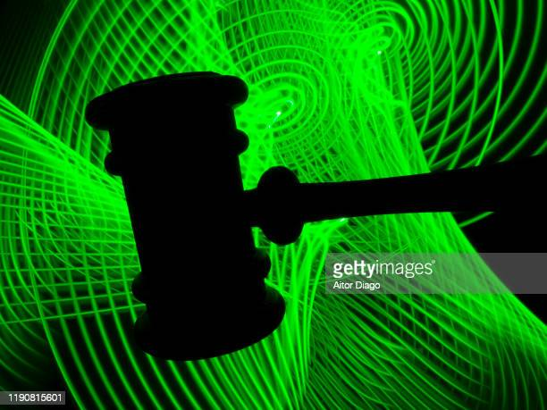 judge's gavel with in a futuristic green background. - sentencing stock pictures, royalty-free photos & images