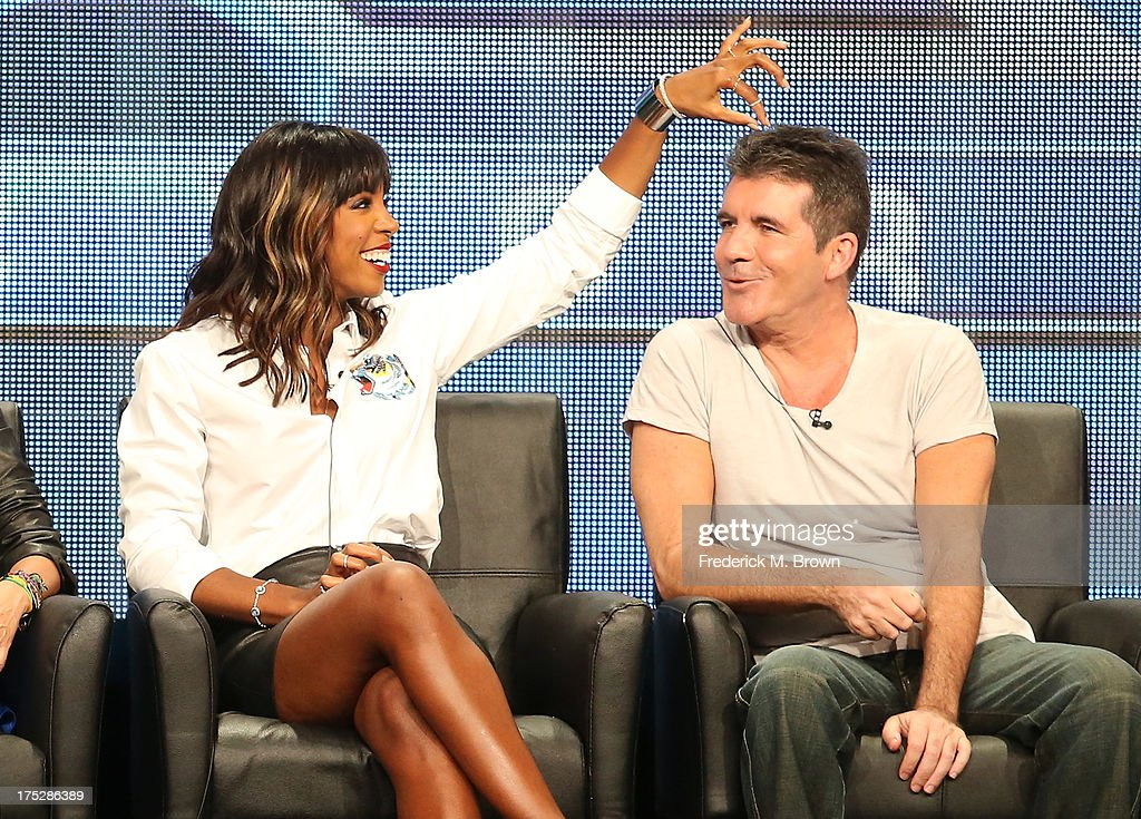 "Judges Kelly Rowland (L) and Simon Cowell speak onstage during the ""The X Factor"" panel discussion at the FOX portion of the 2013 Summer Television Critics Association tour - Day 9 at The Beverly Hilton Hotel on August 1, 2013 in Beverly Hills, California."