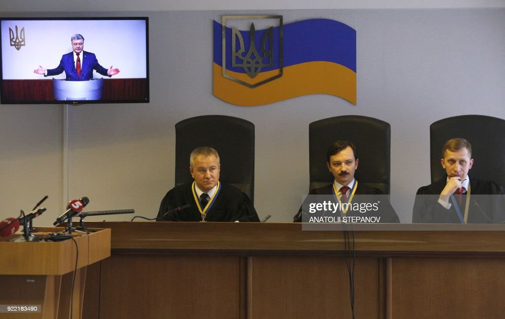 Judges listen as Ukrainian President Petro Poroshenko's testimony is broadcast on a screen as he is questioned during a court hearing in Kiev on February 21, 2018, in the case of Ukraine's ex-president. A Kiev district court questioned Poroshenko through video communication as a witness in the state treason case of ex-president Viktor Yanukovych, who fled to Russia. /