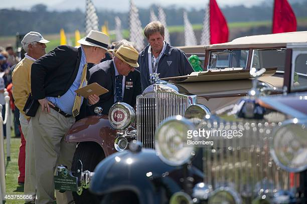 Judges look at an automobile during the 2014 Pebble Beach Concours d'Elegance in Pebble Beach, California, U.S., on Sunday, Aug. 17, 2014. The annual...