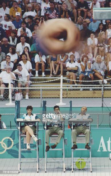 Judges look on as a diver tucks into a blurred roll during the Men's 3 metre springboard event during the XXVI Olympic Summer Games on 28 July 1996...