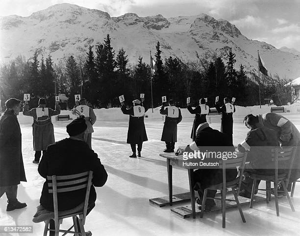Judges of the Women's Singles Skating competition at St Moritz hold up score cards after a performance