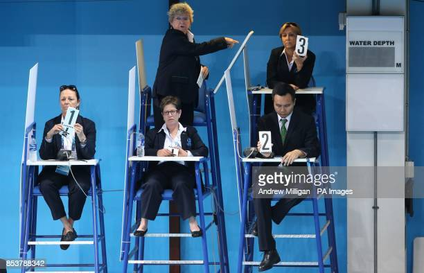 Judges use manual score cards after the automated system failed during the Women's Synchronised 10m Platform Diving Final at the Royal Commonwealth...