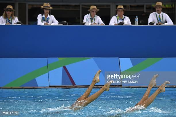 Judges watch Austria's Anna-Maria Alexandri and Austria's Eirini-Marina Alexandri competing in the Duets Technical Routine final during the...