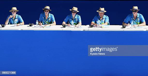 Judges watch the synchronized swimming duet's preliminary competition, with hats and sunglasses necessary under strong sunshine at the Rio de Janeiro...