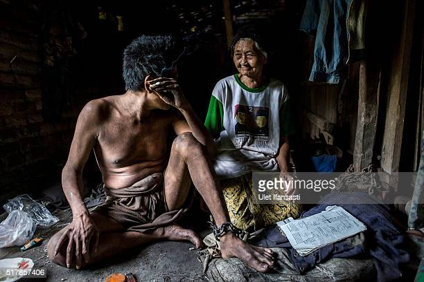 Judi sits on the ground inside his house with his mother Senah as his legs have been chained for 16 years by his parents because he suffers from...