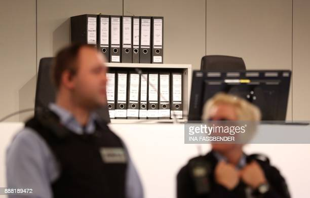Judicial officers stand in front of criminal files in the courtroom on the fairground in Duesseldorf, western Germany, on December 8, 2017 ahead the...