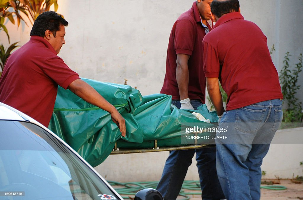 Judicial staffers carry the remains of former Paraguayan general and UNACE party presidential candidate Lino Oviedo, his bodyguard Denis Galeano and pilot Ramon Picco Delmás, who died earlier today in a helicopter crash, upon arrival at the judicial morgue in Asuncion on February 3, 2013. Oviedo, 69, the controversial presidential candidate who helped topple Paraguayan dictator Alfredo Stroessner in 1989, died when the aircraft crashed en route to Asuncion while returning from a campaign rally in northern Paraguay, prompting claims of foul play. AFP PHOTO/Norberto Duarte