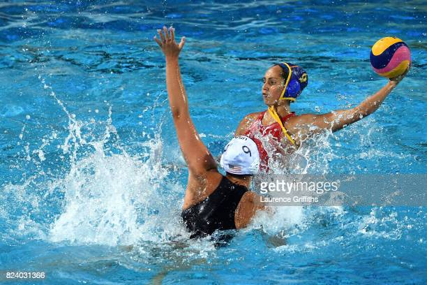 Judith Forca Ariza of Spain shoots past Aria Fischer of United States during the Women's Water Polo gold medal match between the United States and...