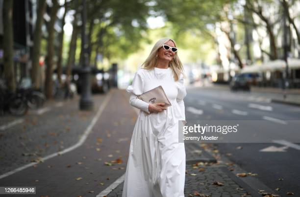 Judith Mosqueira do Amaral wearing Toteme dress, Ariane Ernst earring, Balenciaga sneaker, Hermes clutch and Celine shades on August 14, 2020 in...