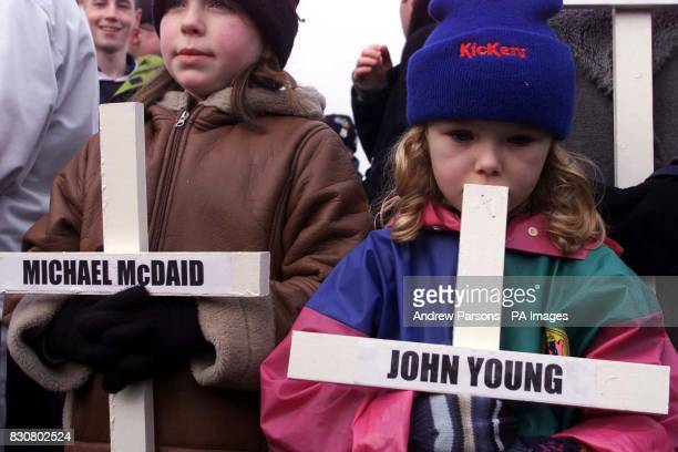 Judith Walker ten and Annie Ward six carrying crosses for thier relatives joins thousands of people on the streets of Londonderry to retrace the...