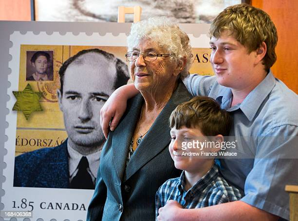 Judith Weiszmann poses in front of a Canada Post Stamp commemorating Raoul Wallenberg with her grandchildren Adrain and Gabriel BrodskyWeizmann at...