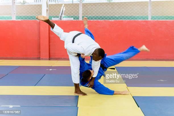 athlète de judo entrant dans le coup pendant le combat - judo photos et images de collection