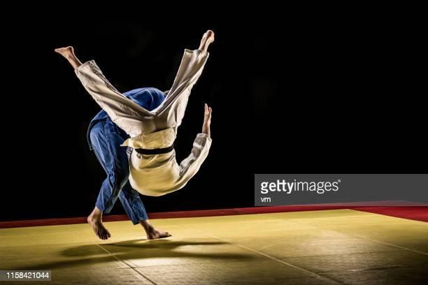praticien de judo dans l'air pendant le jet - judo photos et images de collection