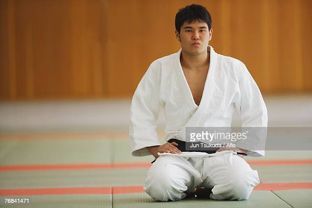 judo student kneeling on mats - 柔道 ストックフォトと画像