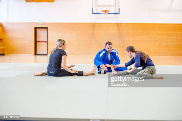 Judo Teacher and Two Young Women Streching Muscles before Training