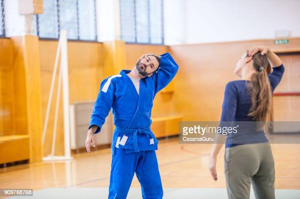 Judo Teacher and Young Woman Streching Muscles before Training