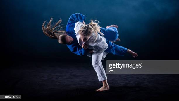 judo throw on black background - judo stock pictures, royalty-free photos & images