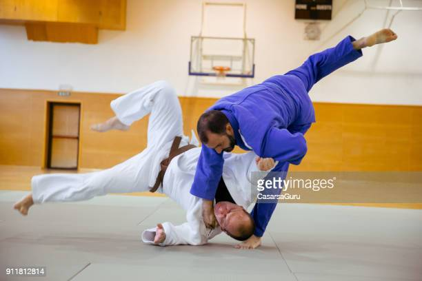 judoist fighters competing in judo match - judo stock photos and pictures