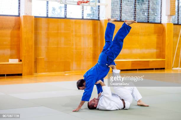 judoist fighters practicing joint lock and chokehold technique - lock sporting position stock pictures, royalty-free photos & images