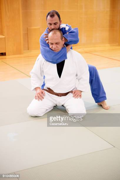 judoist performing rear choke technique - judo stock pictures, royalty-free photos & images