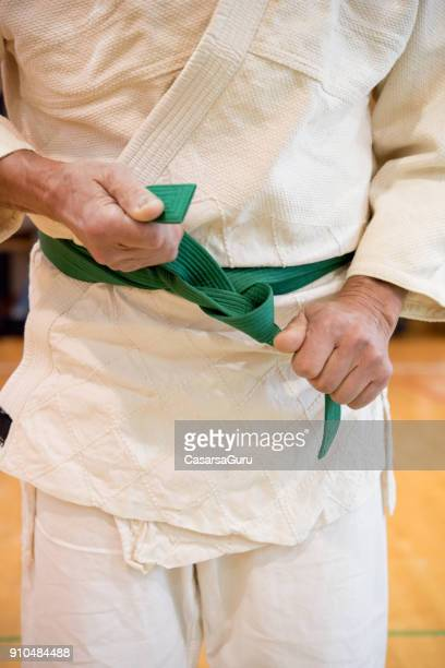 judoist tying up his green belt - judo stock pictures, royalty-free photos & images