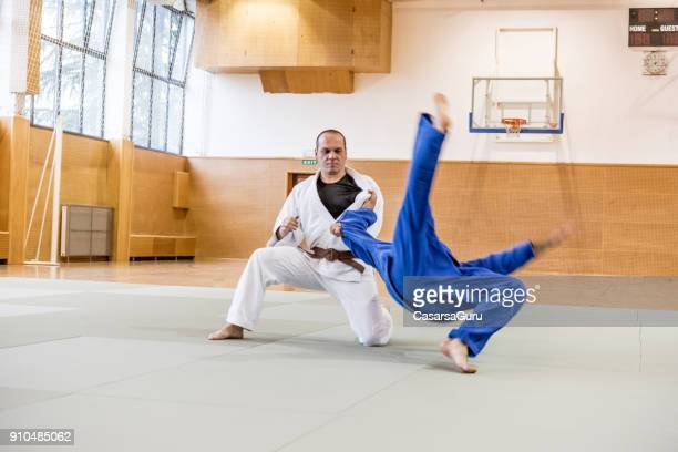 judoist using hand throwing technique - anti gravity stock photos and pictures