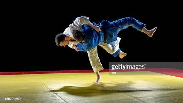 柔道家は、彼のパートナーを地面に投げる - 柔道 ストックフォトと画像