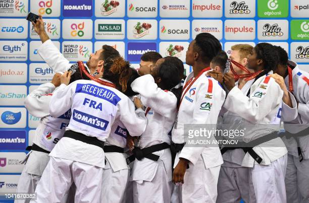 Judokas of the French team pose for a selfie picture with their silver medals during the podium ceremony for the mixed team event of the 2018 Judo...